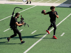 1UP Sports Marketing client Patrick Mahomes about to throw a football and being filmed by a videographer
