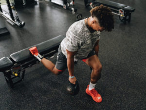 1UP Sports Marketing client Patrick Mahomes working out in the gym with kettlebells