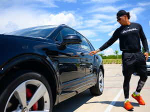 1UP Sports Marketing client Patrick Mahomes reaching for the door of a black Bentley