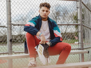1UP Sports Marketing client Patrick Mahomes sitting on bench holding his adidas shoes