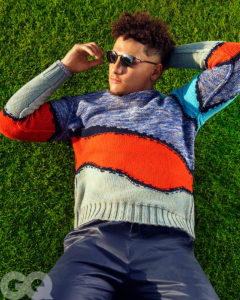 1UP Sports Marketing client Patrick Mahomes lies in the grass wearing sunglasses for a GQ photoshoot