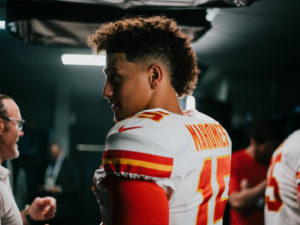 Side shot of 1UP Sports Marketing client Patrick Mahomes in a locker room wearing his jersey