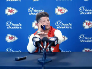 1UP Sports Marketing client Patrick Mahomes talks on his phone at a mock press event during a Head & Shoulders TV commercial