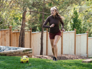 1UP Sports Marketing client Brittany Lynne Matthews kicking a soccer ball outside