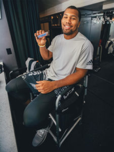 1UP Sports Marketing client Bradley Chubb sits in a chair holding a Snickers bar