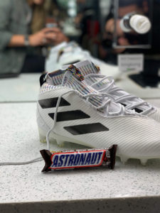 "Snickers bar labeled with ""Astronaut"" leaning up against shoes owned by 1UP Sports Marketing client Bradley Chubb"