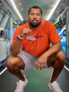 "1UP Sports Marketing client Bradley Chubb kneels with a Snickers ""Hungry"" chain and pendant"