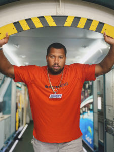 "1UP Sports Marketing client Bradley Chubb poses in a doorway with a Snickers ""Hungry"" chain and pendant"