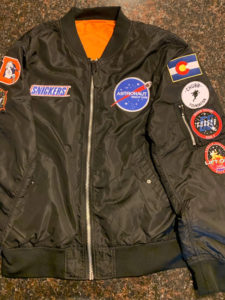 "Jacket of 1UP Sports Marketing client Bradley Chubb, featuring ""Astronaut"" and Snickers"" patches."